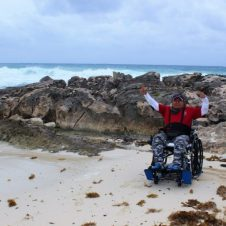 Gabi with hands raised at the rocks by the Caribbean at Chen Rio in Cozumel