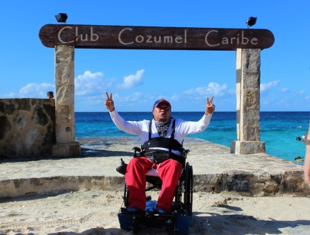 Gabi giving peace signs in front of the Club Cozumel Caribe sign inside of Buccanos Beach Club.
