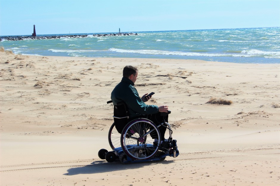 Man at beach with wheelchair on Freedom Trax FT1. Working on his smart phone.