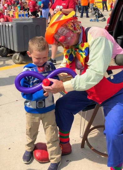 Young boy getting a balloon animal made by a clown
