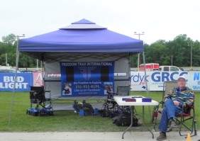 Vendor booth for Freedom Trax International with sign and 3 Freedom Trax mobility devices