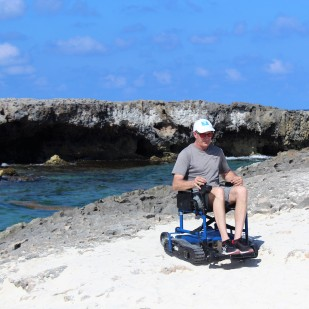 On the beach near the water and rock formations in a Freedom Trax track chair.